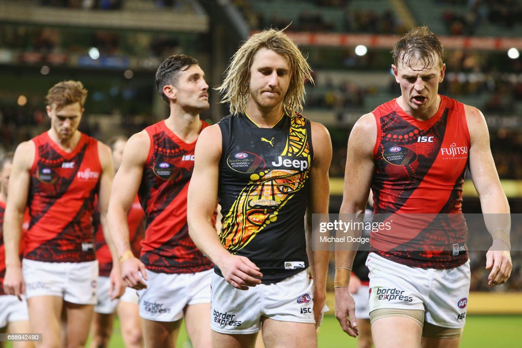 Dyson Heppell of the Bombers walks off wearing a Tigers jumper next to Brendon Goddard of the Bombers after defeat during the round 10 AFL match between the Richmond Tigers and the Essendon Bombers at Melbourne Cricket Ground on May 27, 2017 in Melbourne, Australia.