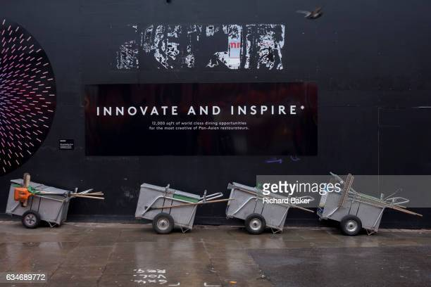 A dystopian landscape of Westminster council sweepers' barrows and an inspirational corporate slogan on a construction hoarding on 31st January 2017...