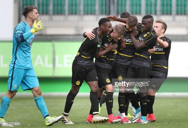 Dzenis Burnic of Dortmund celebrates after scoring his team's third goal with team mates next to goalkeeper Phillip Menzel of Wolfsburg during the...