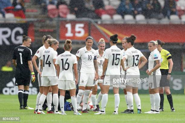 Dzsenifer Marozsan of Germany speaks to the Germany team as Linda Dallmann of Germany receives treatment from the medical team during the UEFA...
