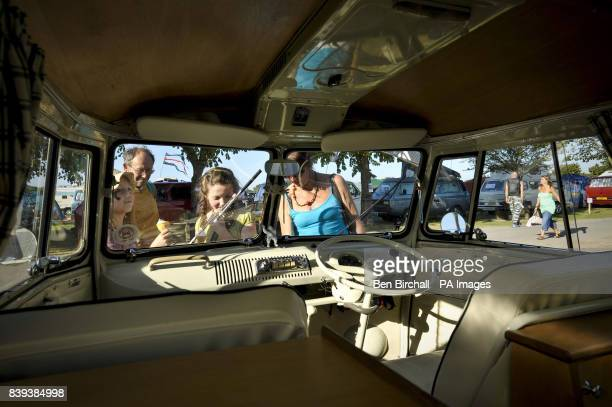 Eager festival goers look through the front windscreen into the cab area of a 1967 VW Splitscreen Type 2 Transporter at Vanfest festival in the Three...