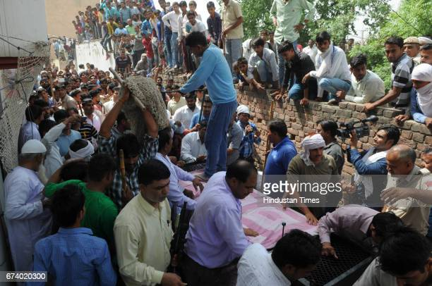 Eager locals come out to see the leopard and get pictures clicked in Durga colony of Sohna on April 27 2017 some 25 km from Gurgaon India