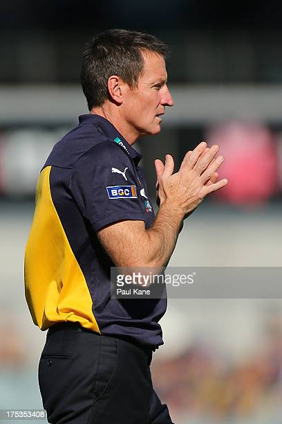 Eagles coach John Worsfold looks on as his players warm up prior to the start of the round 19 AFL match between the West Coast Eagles and the Gold...