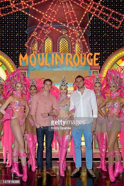 Eamonn Sullivan and Matt Targett pose with the Australian dancers of the Moulin Rouge after they have attended the show at Le Moulin Rouge on July 3...