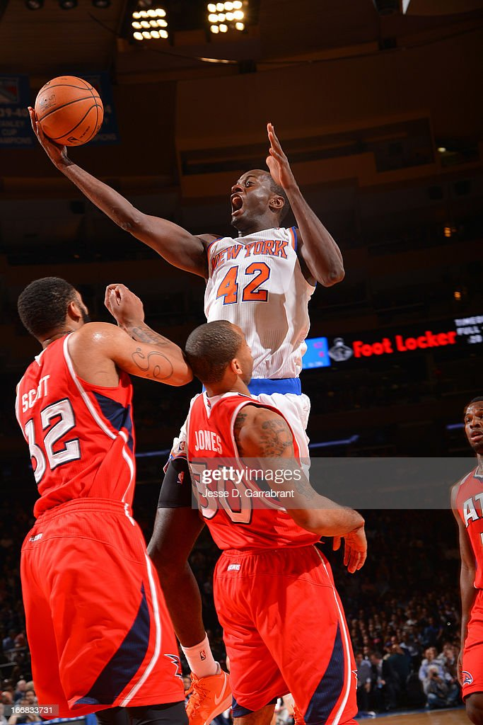 Earl Barron #42 of the New York Knicks shoots a driving layup against Mike Scott #32 and Dahntay Jones #30 of the Atlanta Hawks on April 17, 2013 at Madison Square Garden in New York City, New York.