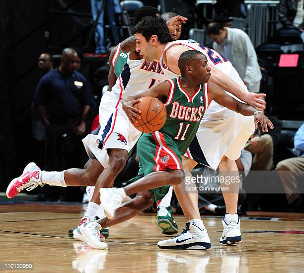 Earl Boykins of the Milwaukee Bucks drives to the basket against Zaza Pachulia of the Atlanta Hawks on March 15 2011 at Philips Arena in Atlanta...