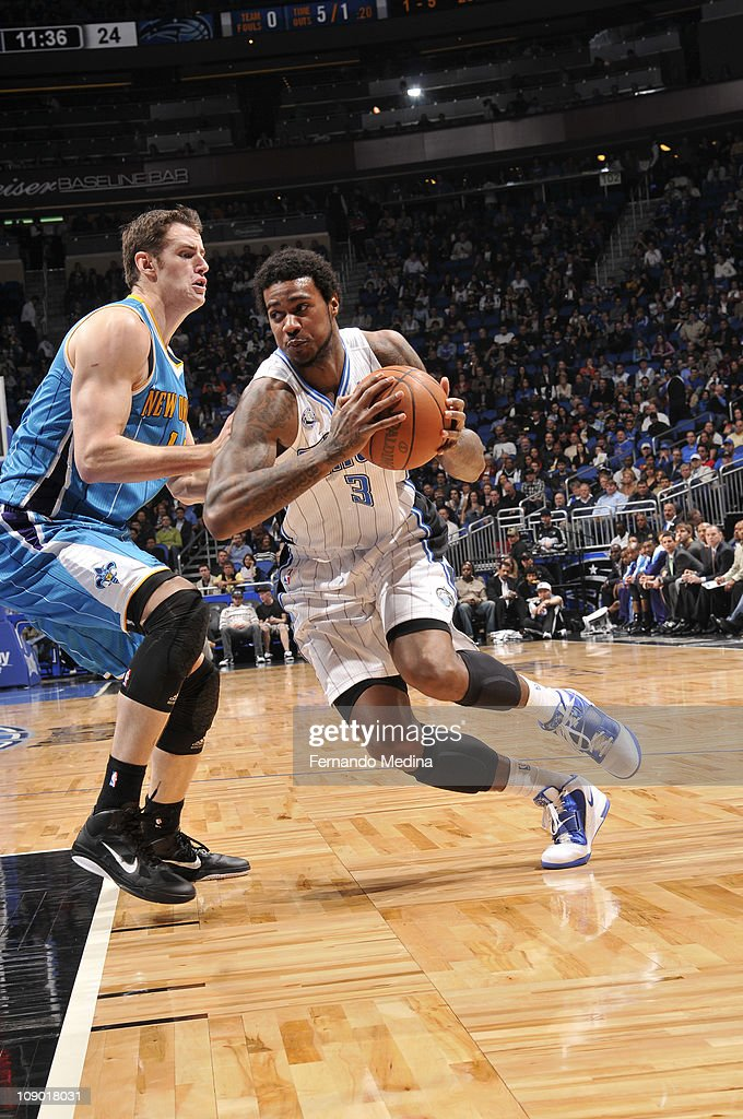 Earl Clark #3 of the Orlando Magic drives to the basket against <a gi-track='captionPersonalityLinkClicked' href=/galleries/search?phrase=David+Andersen+-+Basketball+Player&family=editorial&specificpeople=14914255 ng-click='$event.stopPropagation()'>David Andersen</a> #11 of the New Orleans Hornets during the game on February 11, 2011 at the Amway Center in Orlando, Florida.