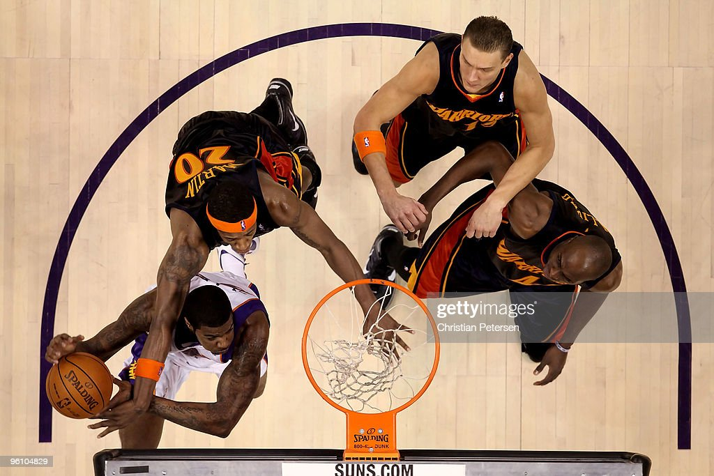 Earl Clark of the Phoenix Suns is fouled as he attempts a shot against Cartier Martin Andris Biedrins and Anthony Tolliver of the Golden State...