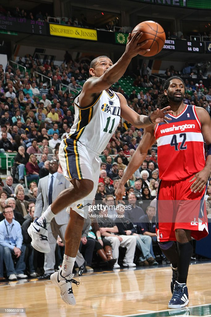 Earl Watson #11 of the Utah Jazz drives to the hoop against Nene #42 of the Washington Wizards at Energy Solutions Arena on January 23, 2013 in Salt Lake City, Utah.