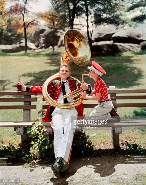 A male model dressed in a red 'band' jacket and white pants sits on a park bench in New York's Central Park holding a CocaCola in one hand and a tuba...