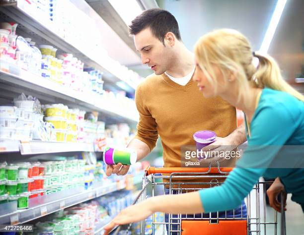 Early 30's man and woman shopping in supermarket.