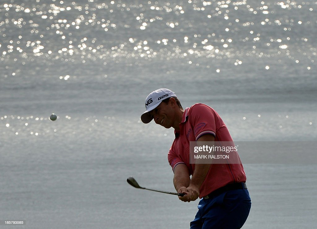 Early leader Luke Guthrie of the US chips onto the green at the 9th hole during day two of the BMW Shanghai Masters golf tournament at the Lake Malaren Golf Club in Shanghai on October 25, 2013. The 7 million USD event is being held for the second time at the Lake Malaren Golf Club. AFP PHOTO/Mark RALSTON