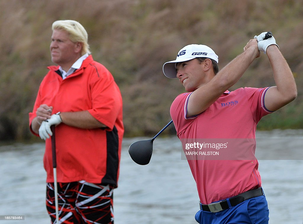 Early leader Luke Guthrie of the US (R) watches his tee shot beside John Daly of the US (L) at the 9th hole during day two of the BMW Shanghai Masters golf tournament at the Lake Malaren Golf Club in Shanghai on October 25, 2013. The 7 million USD event is being held for the second time at the Lake Malaren Golf Club. AFP PHOTO/Mark RALSTON