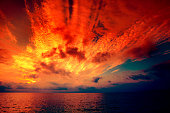 Early morning, burned sunrise over sea. Dramatic sky with red clouds