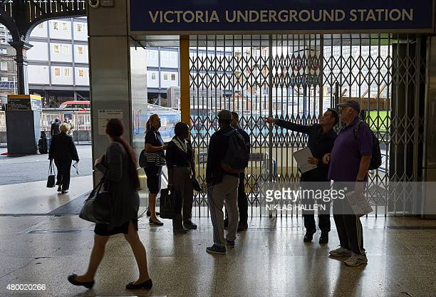 Early morning commuters are given information at a closed underground gate at Victoria station during a tube strike in London on July 9 2015 London's...