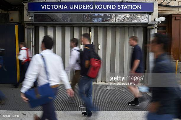 Early morning commuters walk past a closed underground gate at Victoria station during a tube strike in London on July 9 2015 London's roads buses...