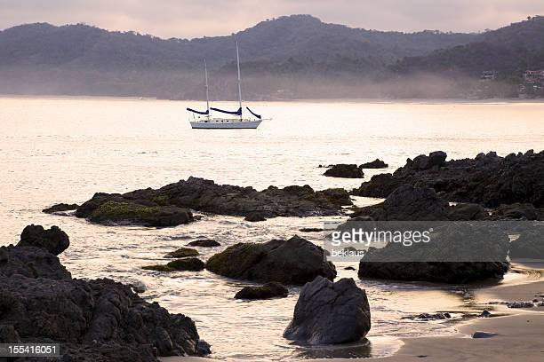 Early morning fog over rocky shore of ocean and sailboat.