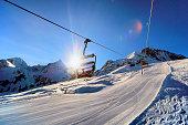 lift view towards rising sun in winter ski resort scenery