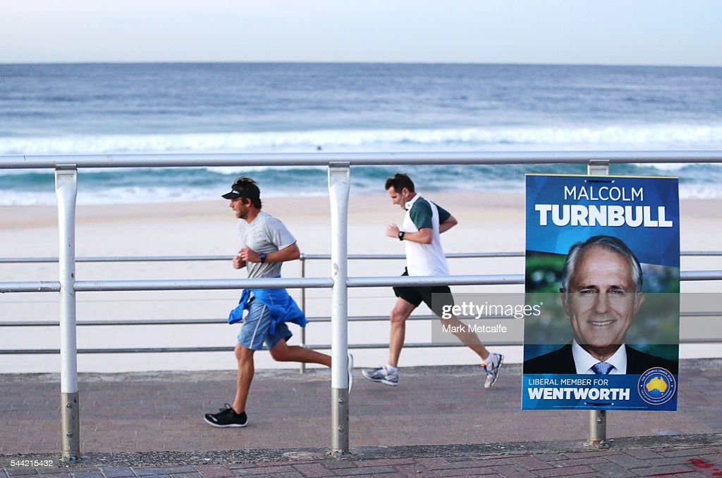Early morning joggers run past election posters at Bondi Beach in the electorate of Wentworth on July 2, 2016 in Sydney, Australia. Voters head to the polls today to elect the 45th parliament of Australia.