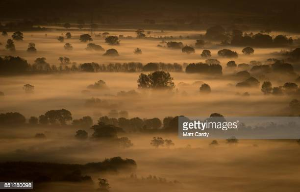 Early morning mist lingers in fields as the autumn sun rises over the Somerset Levels as viewed from Glastonbury Tor near Glastonbury on September 22...