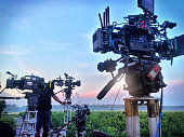 A group of four motion picture cameras set up for a sunrise shot.