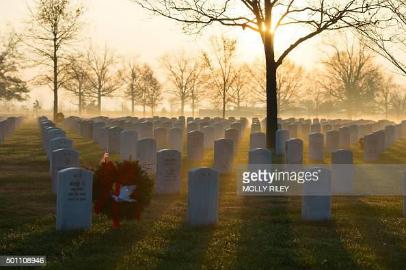 Early morning sun cuts through fog before the start of the 2015 National Wreaths Across America event at Arlington National Cemetery December 12 2015...