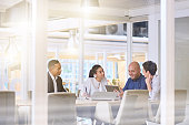 Corporate business meeting in modern office with glass walls, flare from the sunlight and reflections on the glass while business discussions take place amongst board members.