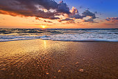 Early morning, sunrise over sea. Golden sands.