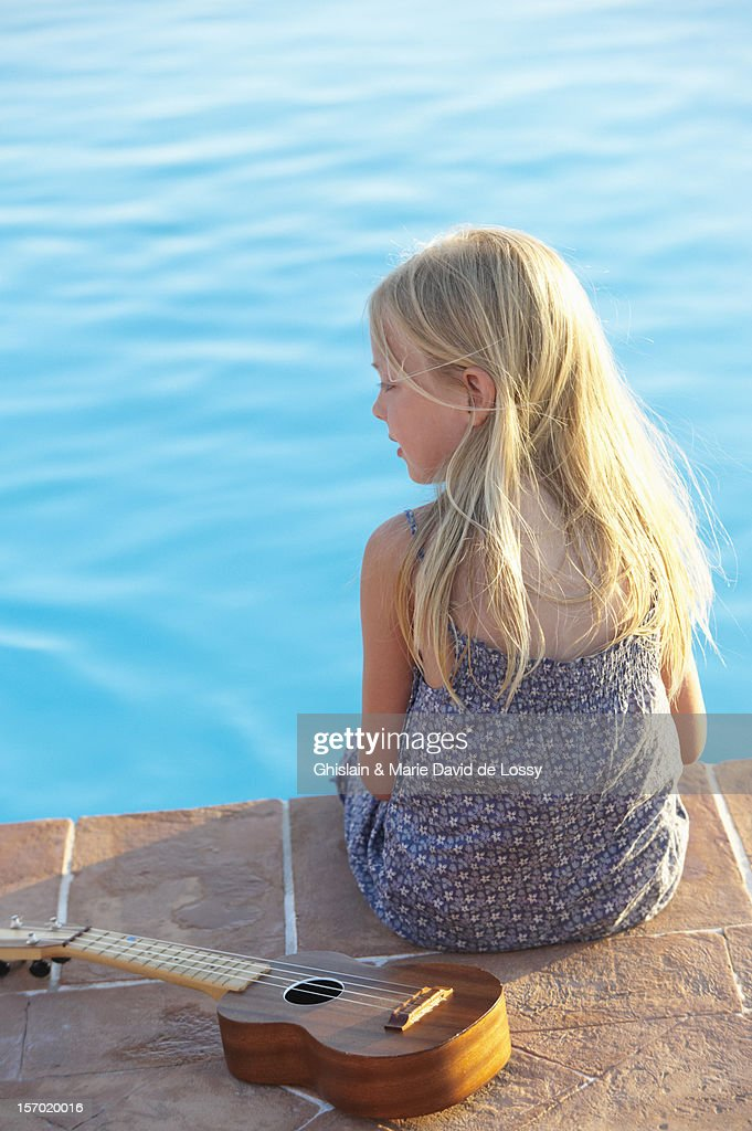 Early teen girl sitting by the pool with ukulele : Stock Photo