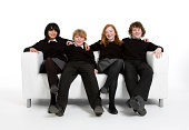 Bright smiles and eye contact from a group of 13 year-old students relaxing together.Full body studio portrait isolated on white.