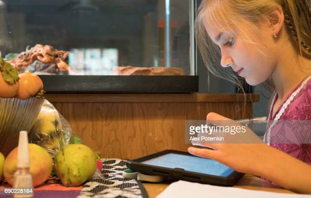 Early teenager girl working with the tablet