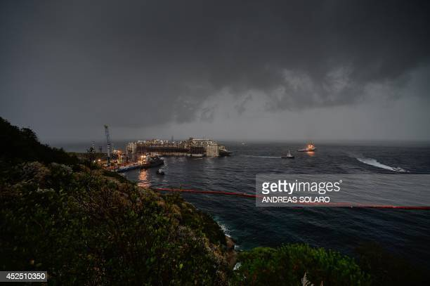 Early view this morning on July 22 over the cruise liner Costa Concordia aground in front of the harbour of Isola del Giglio after being refloated...