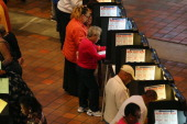 Early voters fill out their ballots as they cast their vote in the presidential election on the first day of early voting at the Stephen P Clark...