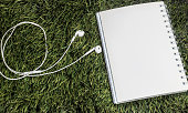 earphone and notebook lay on green grass