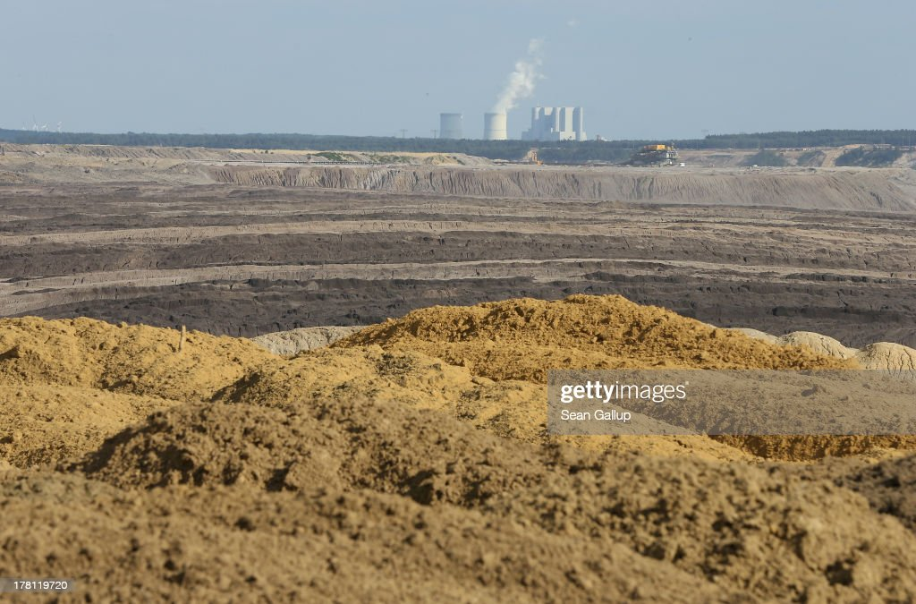 Earth covers a spent portion of the Welzow Sued open-pit lignite coal mine as steam rises from a cooling tower of the Schwarze Pumpe coal-fired power station behind on August 26, 2013 near Welzow, Germany. Welzow Sued, operated by Vattenfall, is among the last active open-pit mines in a region known as the Lausitzer Seenland, where dozens of former mines have been turned into lakes. In a development project initiated by state government, other nearby former open-pit mines that once evoked a lunar landscape are being turned into lakes in a long-term rejuvenation effort that is also intended to make the area a viable tourist destination. Mineral residue in the mines, however, is proving a difficult stumbling block that is making many of the new lakes too acidic to sustain marine life in the short term.