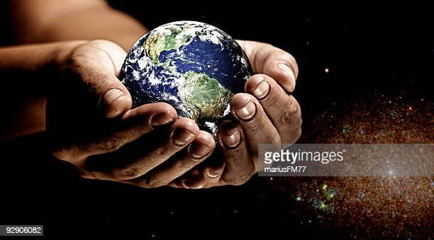 Earth in the palm of two hands with a galaxy background