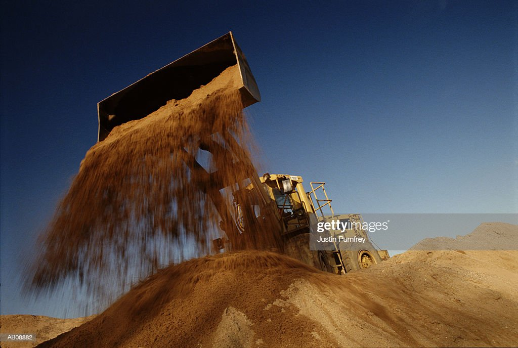 Earth mover in quarry dumping sand, low angle view