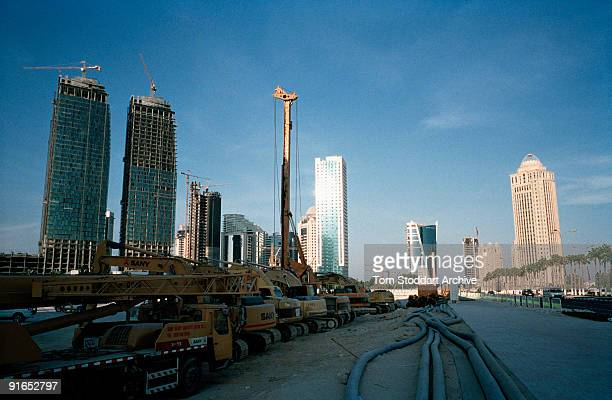 Earth movers at a construction site on the corniche in Doha Qatar May 2008