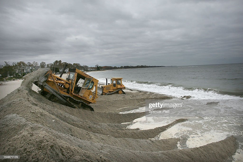 Earth movers build protective berms on Compo Beach as the first signs of Hurricane Sandy approach on October 28, 2012 in Westport, Connecticut. The storm, which could affect tens of millions of people in the eastern third of the U.S., is expected to bring days of rain, high winds and possibly heavy snow in parts of Ohio and West Virginia. New York Governor Andrew Cuomo announced that New York City will close its bus, subway and commuter rail service Sunday evening ahead of the storm.