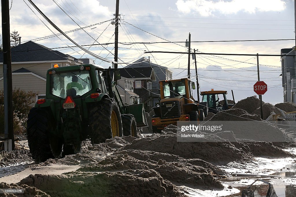 Earth movers push sand off the road that was washed in from Hurricane Sandy on October 31, 2012 in Long Beach Island, New Jersey. Earlier in the week Hurricane Sandy made landfall on New Jersey coastline bringing heavy winds and record floodwaters.