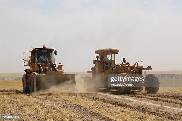 Earth movers work in Arbil on June 10 for the camp which will be built for the Iraqis fleeing Mosul due to the clashes between security forces and...