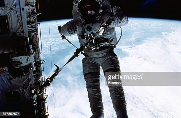 Astronaut F Story Musgrave STS6 mission specialist runs a rope through a snatch block device at the aft bulkhead of the Earthorbiting Space Shuttle...