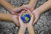 Earth planet in asian Children hand isolated on Ground arid barren- Elements of this image furnished by NASA