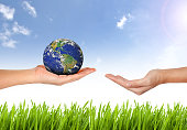 Earth planet the hand on nature and blue sky background - Corporate social responsibility concept. - Elements of this image furnished by NASA