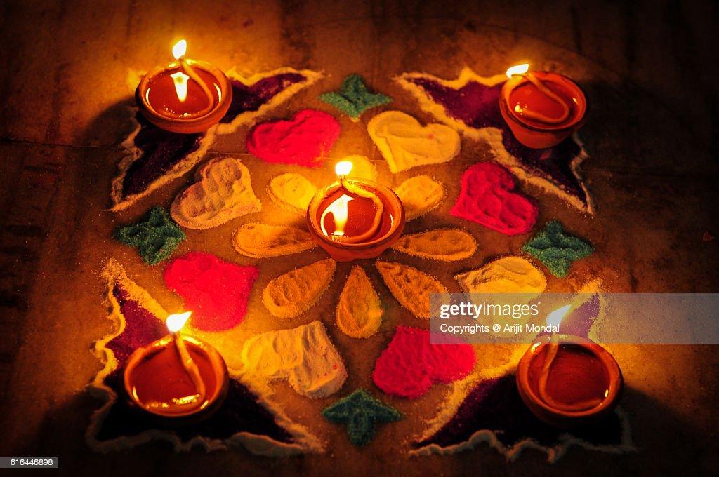 Earthen lamps and Rangoli decoration on floor for Diwali festival : Stock Photo
