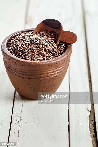 Earthenware dish of organic linseed, Linum usitatissimum, on white wood