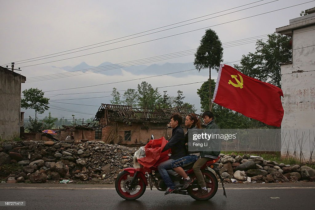 Earthquake survivors carry the flag of the Communist Party of China and ride a motorcycle past a collapsed building after a strong earthquake hit Southwest China's Sichuan Province on April 23, 2013 in Longmen township of Lushan county, China. A magnitude 7 earthquake hit China's Sichuan province on April 20 claiming over 190 lives and injuring thousands.
