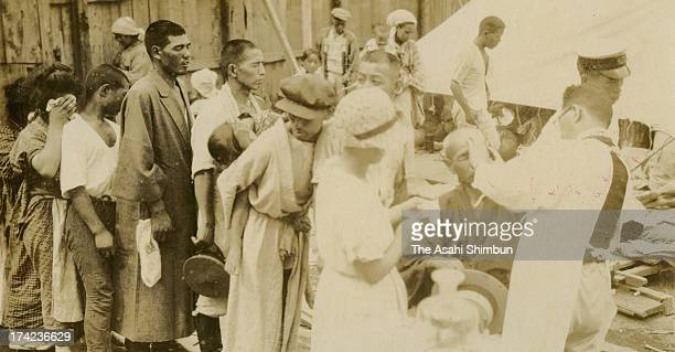 Earthquake survivors queue for medical treatments at a temporary medical center after the Great Kanto Earthquake in September 1923 in Tokyo Japan The...