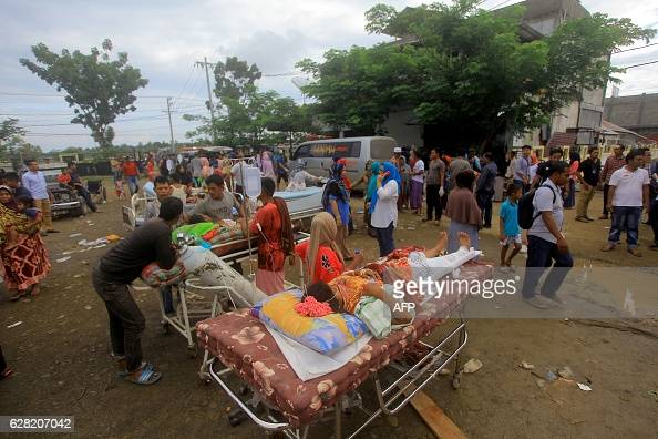 Earthquake survivors receive medical treatment outside a district hospital overloaded with patients in Pidie Jaya Aceh province on December 7 2016 At...