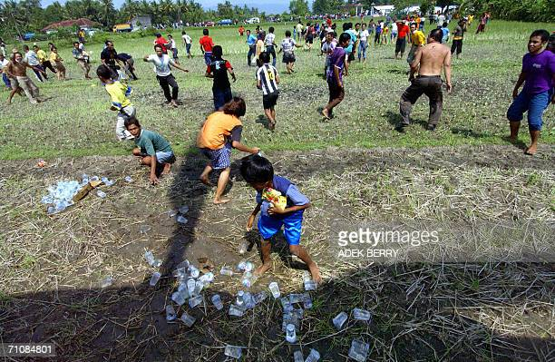 Earthquake victims rush for food and clothing aid as the Indonesian military makes a relief goods supply drop by helicopter at the Bambanglipuro...